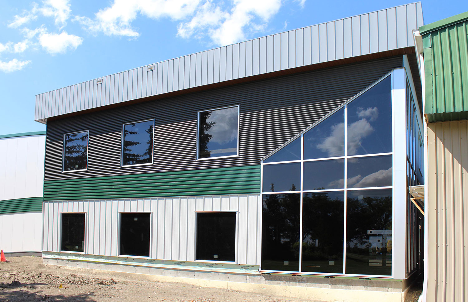 Commercial Building with 7/8 Corrugated in Carbon, Espresso Woodgrain Soffit, and custom panels in Melchers Green and Bright White